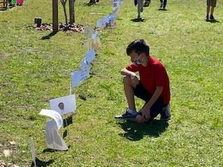 A young boy kneeling on the grass looking at student artwork.