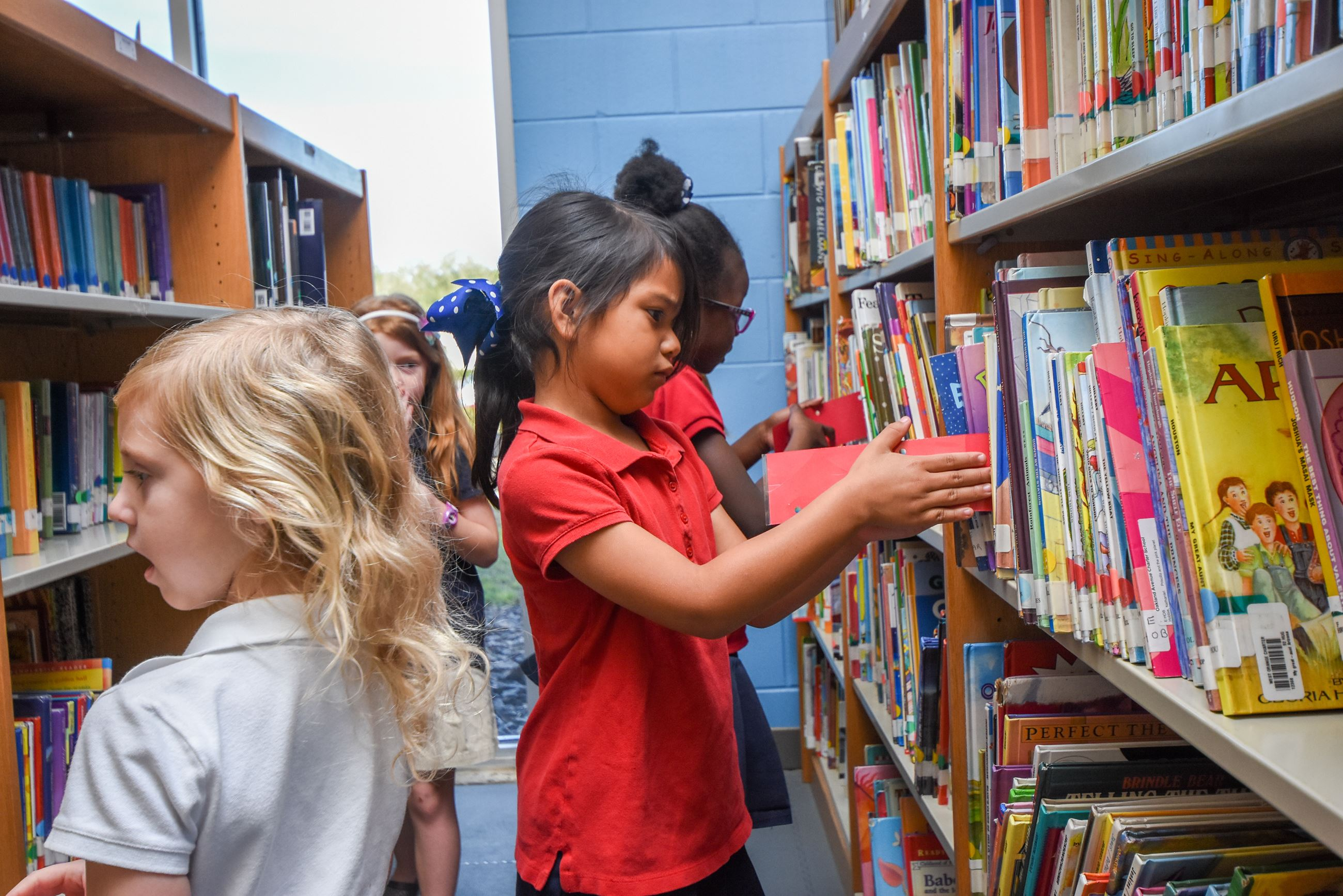 4 girls searching the bookshelves for the perfect library book.